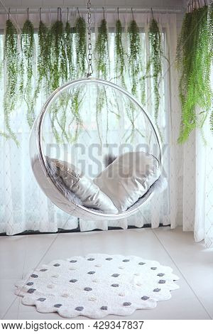 Hanging Chair Made Of Lightweight Material.fastened With Steel Chain In A Room With A Design
