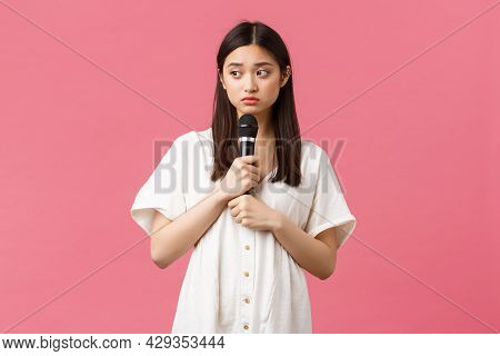 Leisure, People Emotions And Lifestyle Concept. Shy And Worried Cute Asian Girl Holding Microphone A