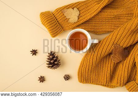 Top View Photo Of Yellow Knitted Pullover Cup Of Tea Brown Autumn Leaves Anise And Pine Cones On Iso