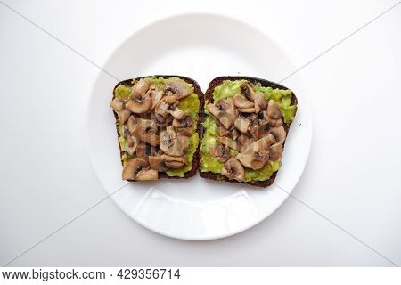 Two Avocado Toast With Fried Mushrooms In A White Plate On A White Background. Top View. Healthy Foo