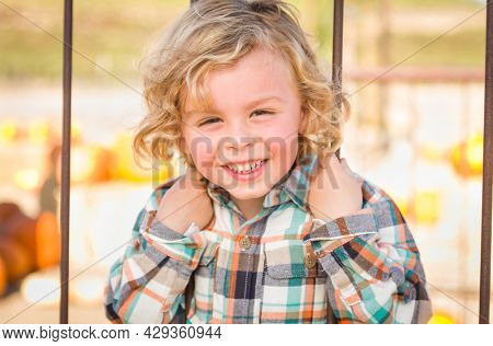 Little Boy Having Fun in a Rustic Ranch Setting at the Pumpkin Patch.