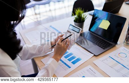 At Bright Modern Office, Bank Office Or Businesswoman Working With Calculator, Laptop, Company Docum