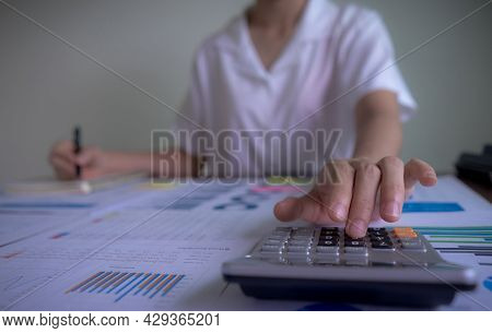 Close Up, Businesswoman Hand Using Calculator And Writing Make Note With Calculate About Cost, Tax,