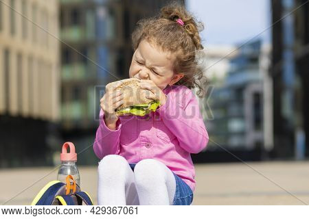 Hungry Cute Girl, Junior Schoolgirl With Appetite Eating Homemade Sandwich Between Classes On Campus