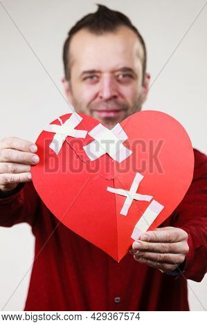 Healed Love. Valentines Day Concept. Adult Smiling Man Holding Big Red Heart Fixed With Plaster Band