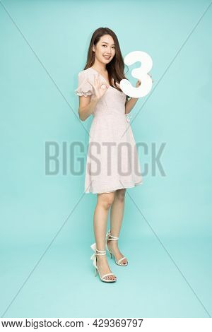 Young Beautiful Asian Woman Showing Number 3 And Pointing Up With Finger Number Three Isolated On Gr