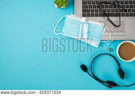 Top View Photo Of Glasses Two Medical Facemasks Sanitizer Bottle On Laptop Binder Clip Headphones Pl
