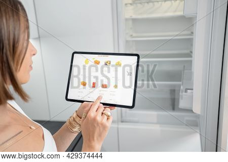 Woman Shopping Groceries Online Using Digital Tablet While Standing Near The Empty Fridge On The Kit