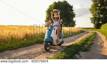The father and son spending time together riding through the field by pathway on the retro scooter in the sunset