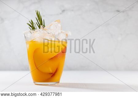Healthy Summer Juice - Peach Cocktail With Ice, Rosemary Twig, Sugar Rim, Fruit Slices In Misted Gla