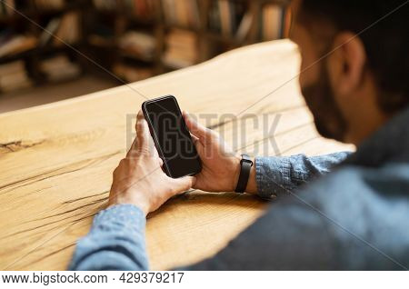 Indian Bearded Man Holding A Black Mobile Phone With Blank Screen, Using New Mobile App, Male Hand W