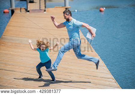 Feel Free To Jump. Energetic Father And Son Jump On Pier. Family Fun