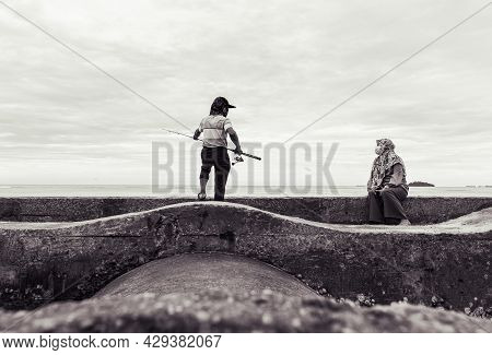 Port Dickson, Malaysia - December 15, 2020: Young Man And His Wife Fishing On A Breakwater On The Be