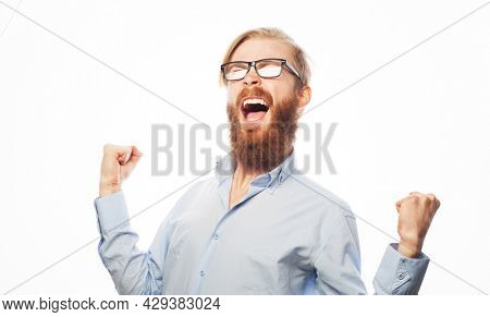 Yeah. Happy winner. Young handsome bearded man wearing eyewear gesturing and keeping mouth open over white background.