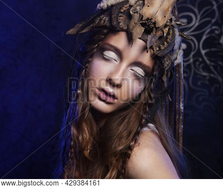 High fashion model with creative hairstyling and bright make up over dark background. Closed eyes. Party time, carnival and halloween theme.