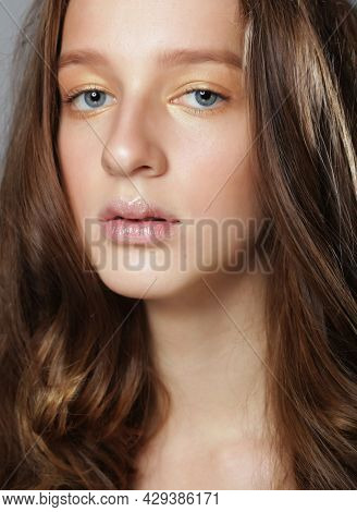 Close up picture of young woman with long and shiny wavy hair. Beautiful model with curly hairstyle. Close up.