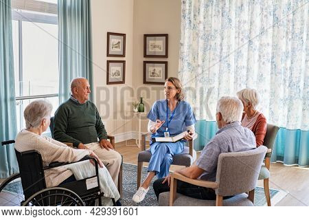 Group of senior people listening to young nurse. Psychological support group for elderly and lonely people in a community centre. Group therapy in session sitting in a circle in a nursing home.