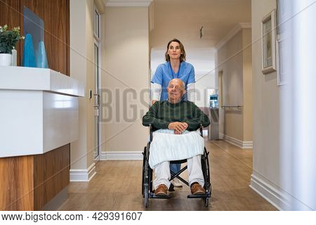 Nurse helping old man in wheelchair in nursing home. Healthcare worker taking care of an elderly disabled patient at care facility centre. Caregiver pushing old patient sitting on a wheelchair.