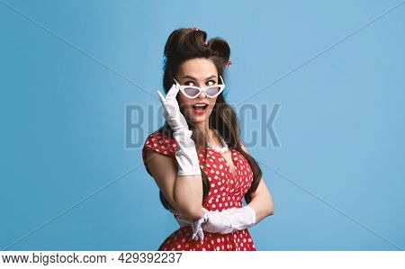 Charming Young Woman In Pinup Outfit Touching Sunglasses, Looking Aside On Blue Background