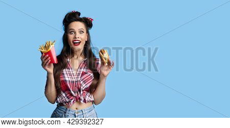 Portrait Of Excited Young Pinup Lady In Retro Outfit Holding Hamburger And French Fries On Blue Back