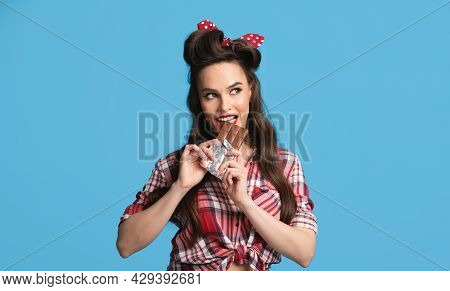 Sexy Millennial Pinup Woman In Retro Outfit Eating Chocolate Bar On Blue Studio Background, Panorama