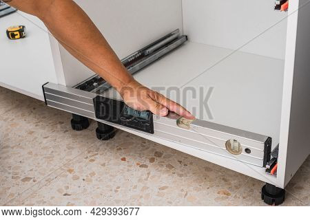 Man Using A Spirit Level To Check The Installation Of Furniture