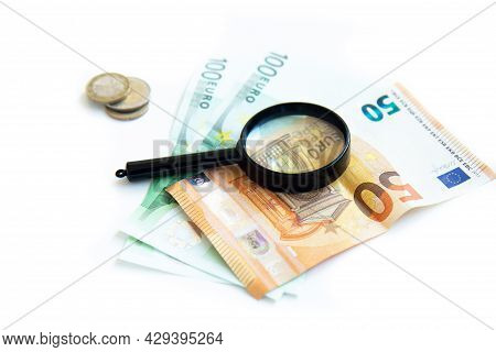 Magnifier, Paper Money And A Stack Of Coins Isolated On White Background. Concept Of Keeping Money,