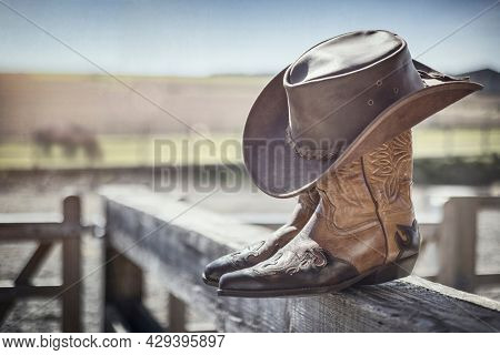 Country music festival live concert with cowboy hat and boots by ranch stables