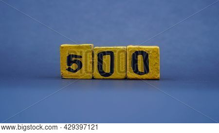 Wooden Block With Number 500. Yellow Color On Dark Background. Focus Selected