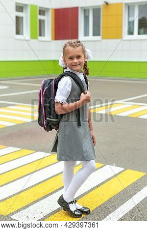 Back To School. A Girl With School Backpacks Goes To School, Smiles And Looks At The Camera. A Child