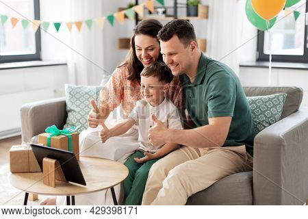 family, holidays and people concept - portrait of happy mother, father and little son with tablet pc computer and birthday gifts on table having video call at home party and showing thumbs up