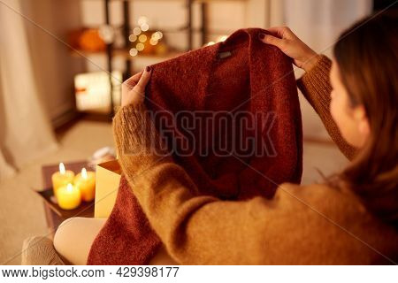 halloween, holidays and leisure concept - close up of young woman taking woolen cardigan from shopping bag at cozy home