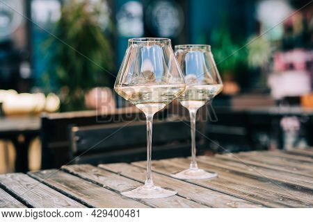 A Wooden Table In A Restaurant With White Wine. Wine Glasses Served For A Party In A Bar Or A Restau