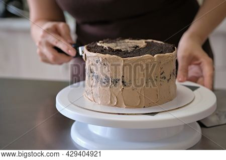 Woman Pastry Chef Making Chocolate Cake With Chocolate Cream, Close-up. Cake Making Process, Selecti