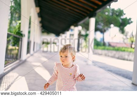 Little Girl Stands In A Long Pavilion