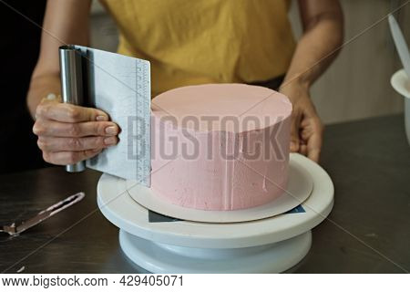 Woman Spreads Pink Cream On Cake, Close-up. Cake Making Process, Selective Focus