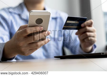 A Woman Holding A Cell Phone And Credit Card, She Fills In Her Credit Card Information In A Mobile S