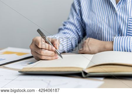 A Woman Is Taking Notes In A Notebook, She Works From Home Due To The Epidemic, She Records Details
