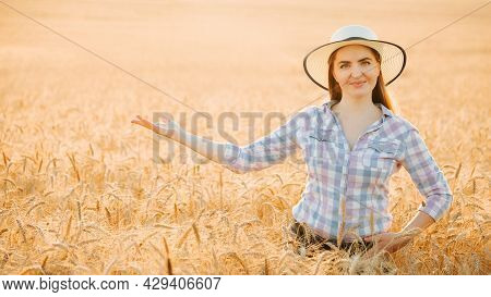 Portrait Of Smiling Beautiful Female Farmer With Outstretched Hand. Woman At Wheat Field In Summer D