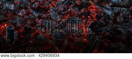 Burning Coals In The Dark, Smoldering Coal. Bright Red Sparks Of Fire. Background.