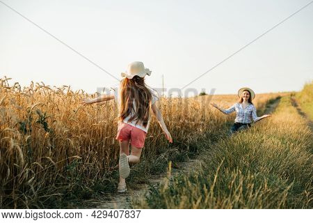 Happy Farmer Mother With Hat Waiting For Her Happy Running Girl. Childhood In Rural Happiness. Famil