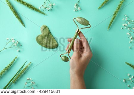 Skin Care Concept With Face Roller And Gua Sha On Mint Background
