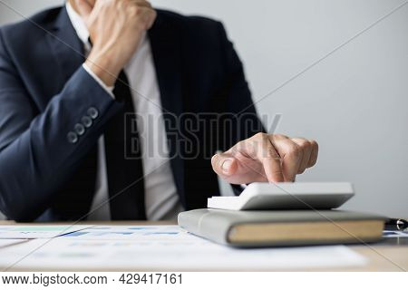 A Man In A Suit Is Pressing A Calculator, A Business Man Sitting In A Private Office At A Company, H
