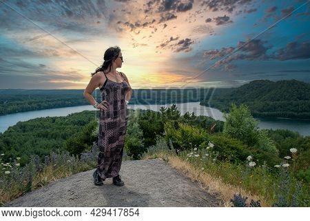 Fashionable Woman Of 30-40 Years Old Outdoors Standing Tall On A Hill With A River Running Through T