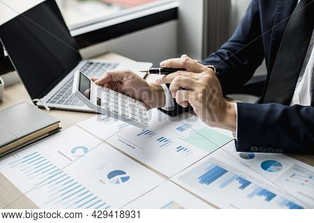 A Man With A Pen Pointing To A White Calculator And Documents Are Placed On The Table, A Businessman
