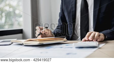 Businessman Takes Notes On A Topic That Examines Information From Finance Documents To Bring To Depa