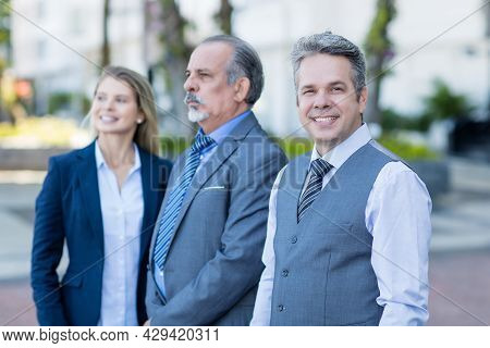 Laughing Mature Adult Businessman With Senior Manager And Young Female Trainee Outdoor In City In Su