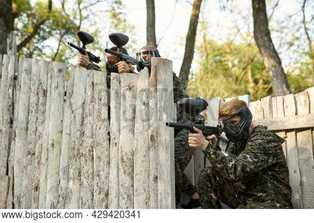 Paintball team shoots with guns, military game