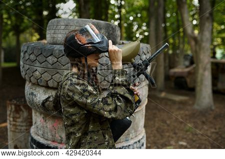 Female paintball player on playground in forest