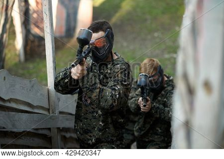 Paintball players aimimg with guns from shelter